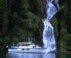 A comfortable motoryacht moored in front of a waterfall